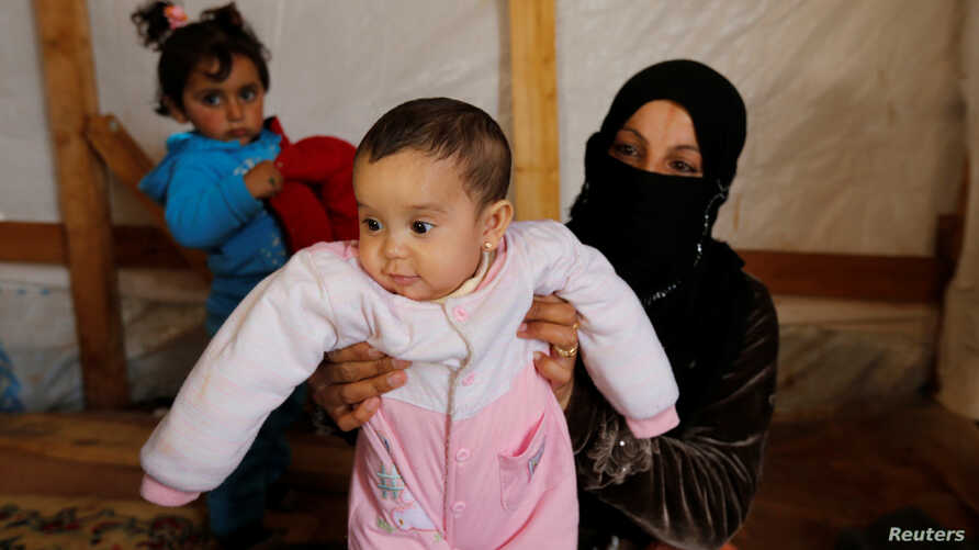 Syrian refugee Asheqa holds her unregistered baby daughter Nour inside a tent at a refugee camp near the town of Baalbek in Lebanon's Bekaa valley, March 3, 2016.
