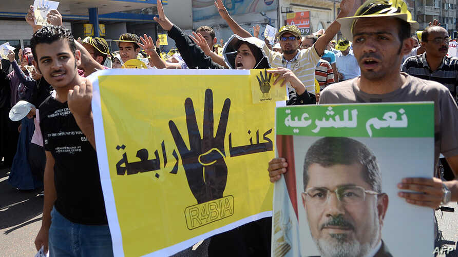 """Supporters of Egypt's ousted Islamist president Mohamed Morsi hold posters of the four finger symbol, known as """"Rabaa"""", which means four in Arabic, to remember those killed in the crackdown on the Rabaa al-Adawiya protest camp in Cairo earlier in the"""