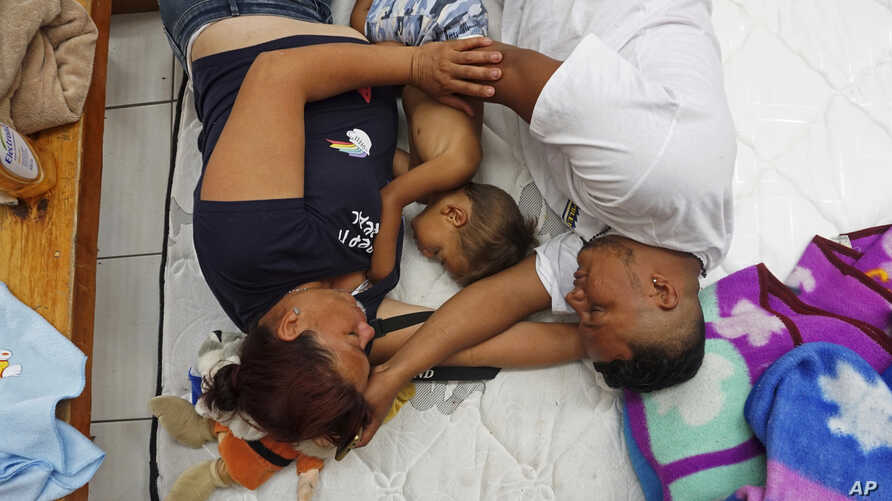 Honduran family Nolvia Luja, left, Willian Bonilla, and their son Wilmer Bonilla, who attended the annual Migrants Stations of the Cross caravan for migrants' rights, rest at a shelter in Tlaquepaque, Jalisco state, Mexico, April 18, 2018.