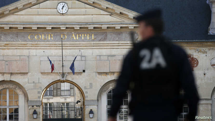 FILE - A police officer secures the entrance of the Appeals Court of Versailles for the arrival of vehicles transporting Mehdi Nemmouche, 29, the French national who is suspected of the shooting attack in the Brussels Jewish Museum in May that left f