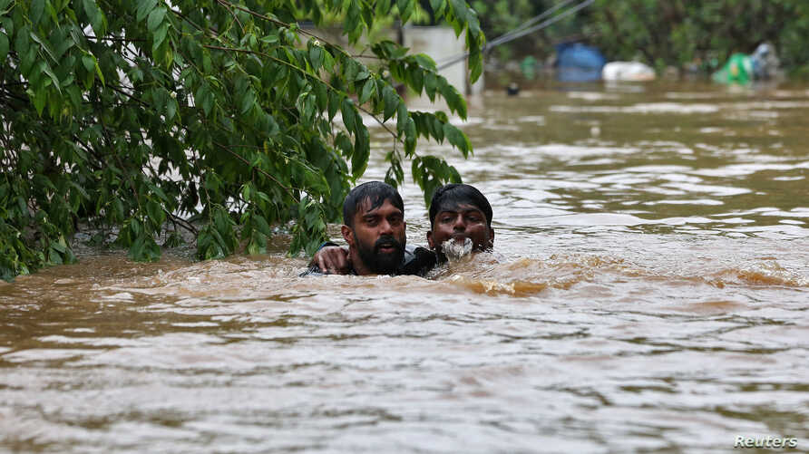 FILE - A man rescues a drowning man from a flooded area after the opening of Idamalayr, Cheruthoni and Mullaperiyar dam shutters following heavy rains, on the outskirts of Kochi, India August 16, 2018.