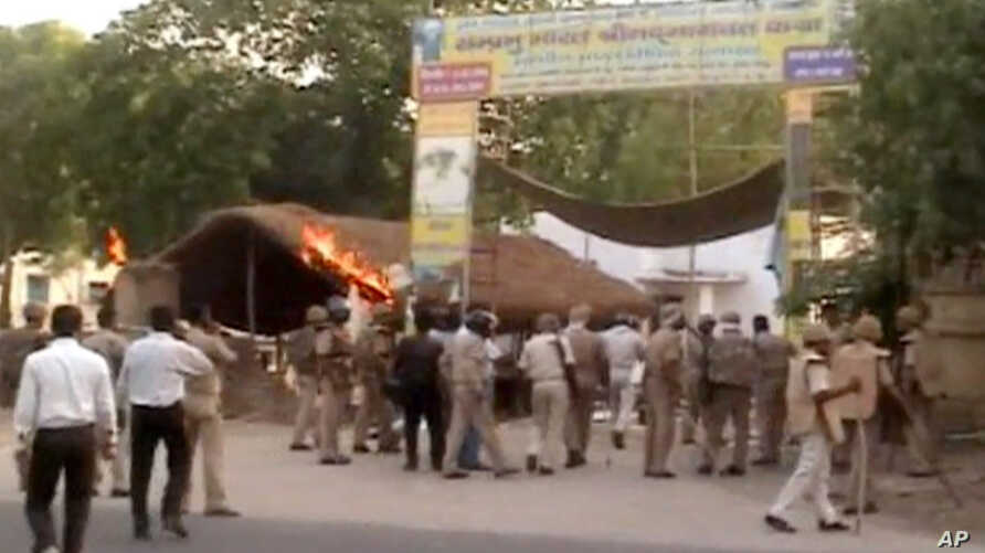 This Thursday, June 2, 2016 image made from video shows Indian policemen and paramilitary soldiers near the site of violent clashes in Mathura, India.