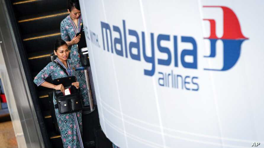 A Malaysia Airlines flight crew heads for the departure lounge at Kuala Lumpur International Airport. Malaysian civil aviation authorities officially declared the airline's Flight MH370 crash an accident on Jan. 29, 2015.