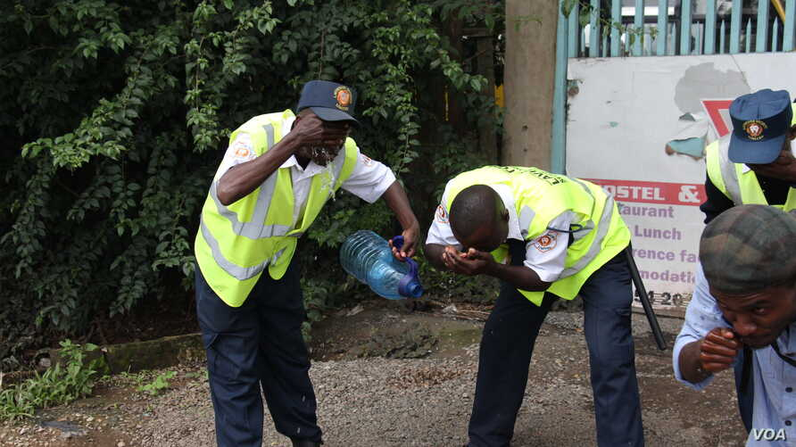 Guards at a nearby building in university road in central Nairobi wash away tear gas. (VOA/ M. Yusuf)
