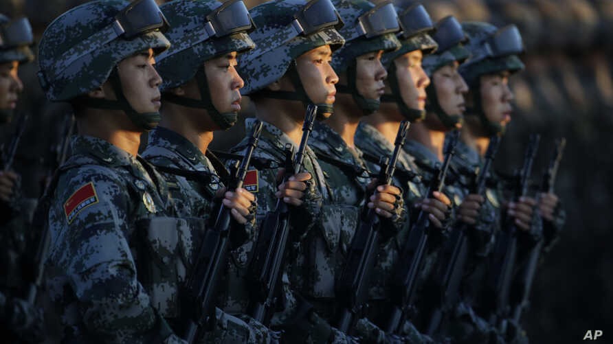 FILE - Soldiers of China's People Liberation Army (PLA) stand in line in front of Tiananmen Gate ahead of a military parade to commemorate the 70th anniversary of the end of World War II in Beijing.