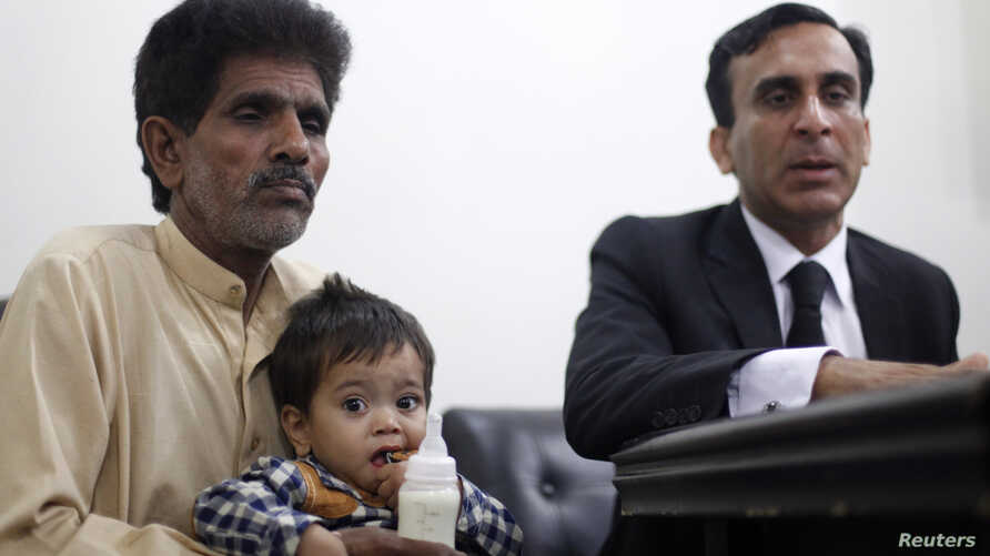 Nine-month-old baby Musa Khan sits on his grandfather's lap before appearing in a court in Lahore April 12, 2014.