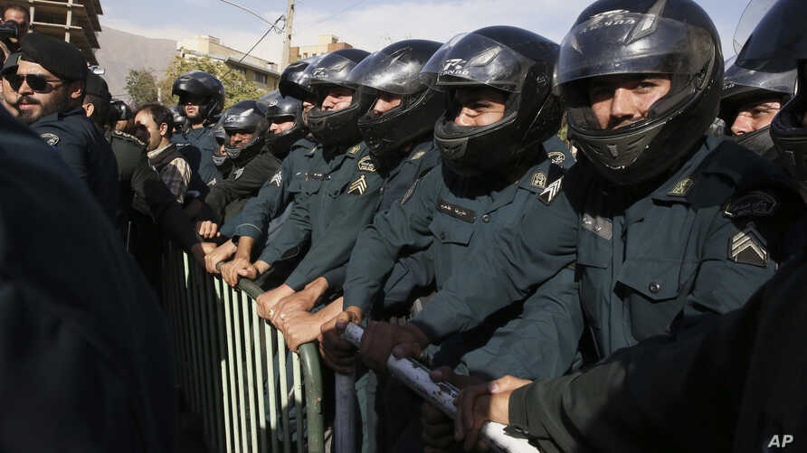 Iranian police officers protect the Saudi Arabian Embassy in Tehran, Iran, Sunday, Sept. 27, 2015, during a gathering of protesters blaming the Arab country for a deadly stampede on Thursday that killed more than 700 pilgrims. Iran's hajj agency on S