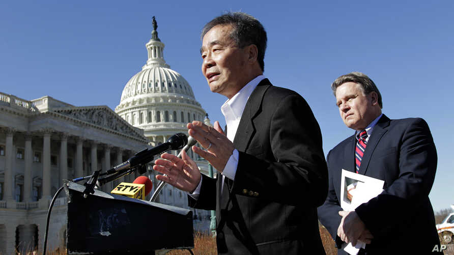 Rep. Chris Smith, R-N.J., right, listens as he and human rights activist Harry Wu, left, criticize the one-child rule in China, at the Capitol in Washington, Monday, March 7, 2011.