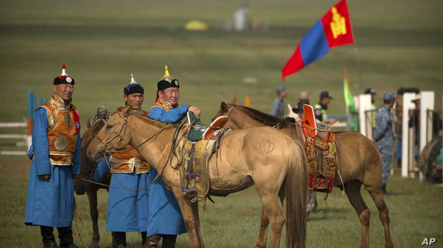 Mongolian horsemen in traditional outfits stand with their mounts before a horse racing competition during the second day of the Naadam Festival in Khui Doloon Khudag, on the outskirts of Ulaanbaatar, Mongolia, July 12, 2016.
