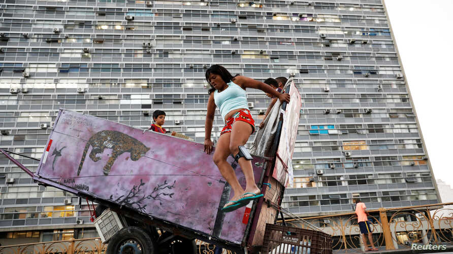Fabiana Silva, 38, a former crack user who now collects recyclable materials, jumps off her cart loaded with recyclables in Sao Paulo, Brazil, June 29, 2017.