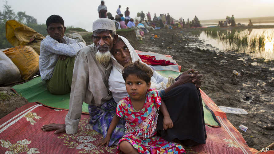Rohingya man Nur Ahmad, 70, his wife Lalu Bibi and their grand daughter Ashuka Bibi, 5, who crossed over to Bangladesh the previous day, wait for permission to go to the refugee camps after spending the night in the rice fields near Palong Khali, Ban...