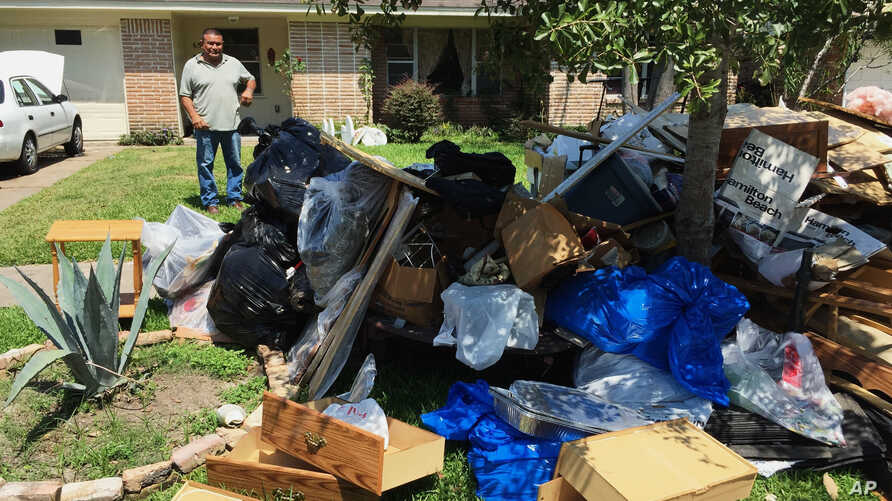 Salvador Cortez, 58, shows debris in the front yard of his home in Houston, Texas, Sept. 9, 2017.