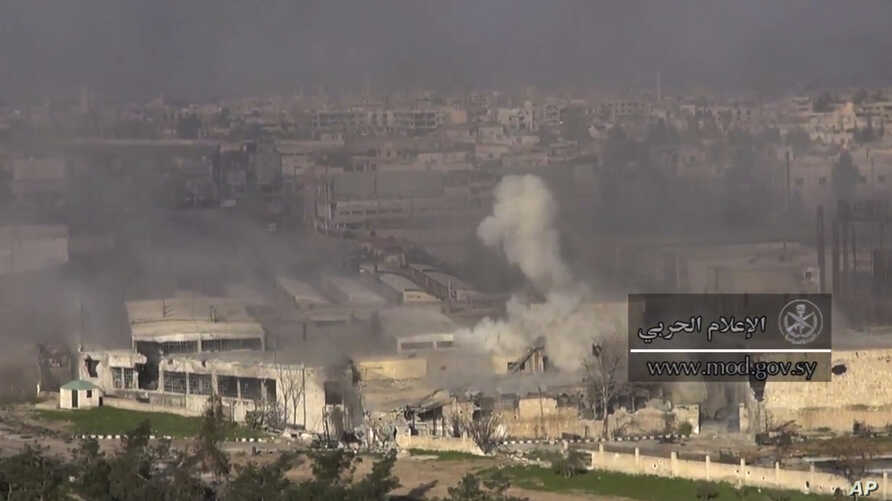 This frame grab from video provided by the government-controlled Syrian Central Military Media, shows smoke rising during fighting between insurgents and Syrian government troops, in an eastern neighborhood of Damascus, Syria, March. 22, 2017.
