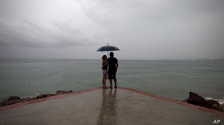 FILE - A couple looks out to sea as rainfall increases on the Pacific coast near Puerto Vallarta, Mexico, Oct. 23, 2015. A tropical depression formed off Mexico's southern Pacific coast Wednesday, prompting authorities to issue a tropical storm warni