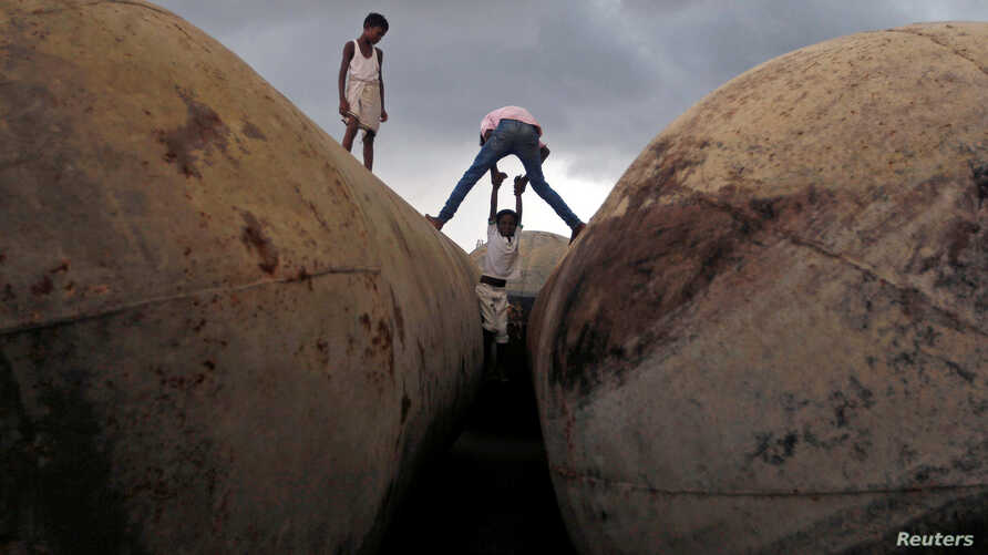 Children play on pontoons as clouds gather over the banks of the river Ganges in Allahabad, India.