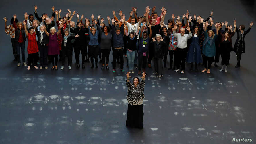 Cuban artist Tania Bruguera stands in the middle of her Hyundai Commission, Our Neighbors, artwork in the the Turbine Hall of Tate Modern, in London, Britain, Oct. 1, 2018. Volunteers stand behind her after lying down on the heat sensitive artwork.