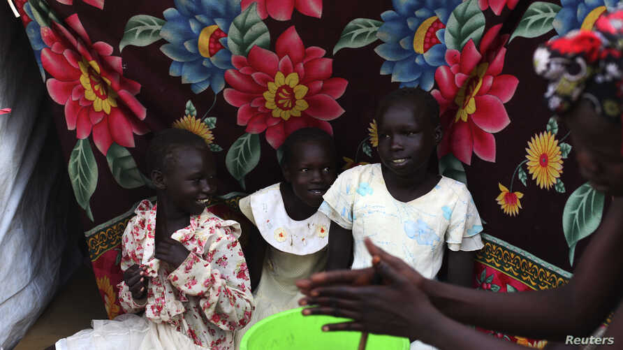 South Sudanese girls, who have been displaced by the fighting, sit by a tent in a camp for displaced persons in the United Nations Mission in South Sudan (UNMISS) compound in Tongping in Juba, February 19, 2014. Thousands of people have been killed a