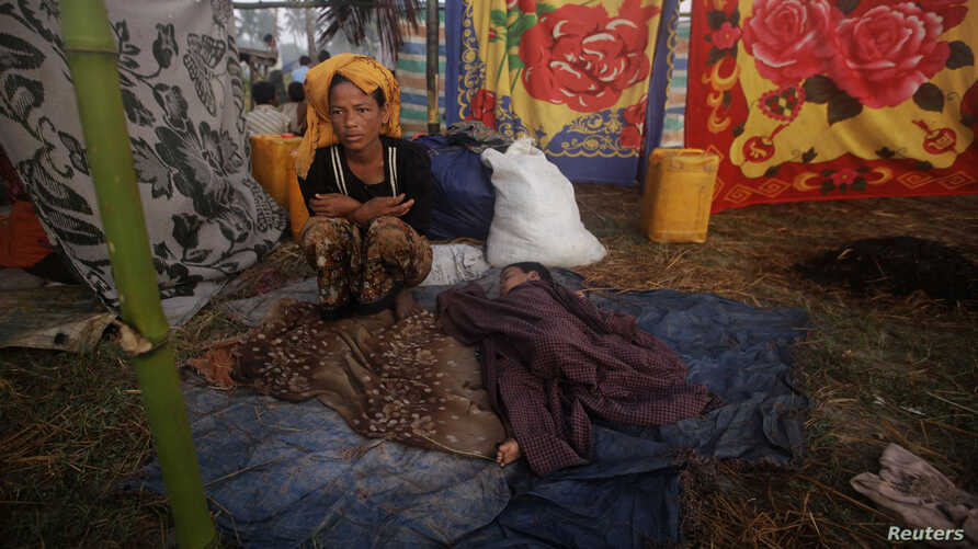 A woman displaced by the recent violence in Pauktaw sits by her sleeping child at Owntaw refugee camp for Muslims outside Sittwe, Rakhaine state, Burma, November 1, 2012.