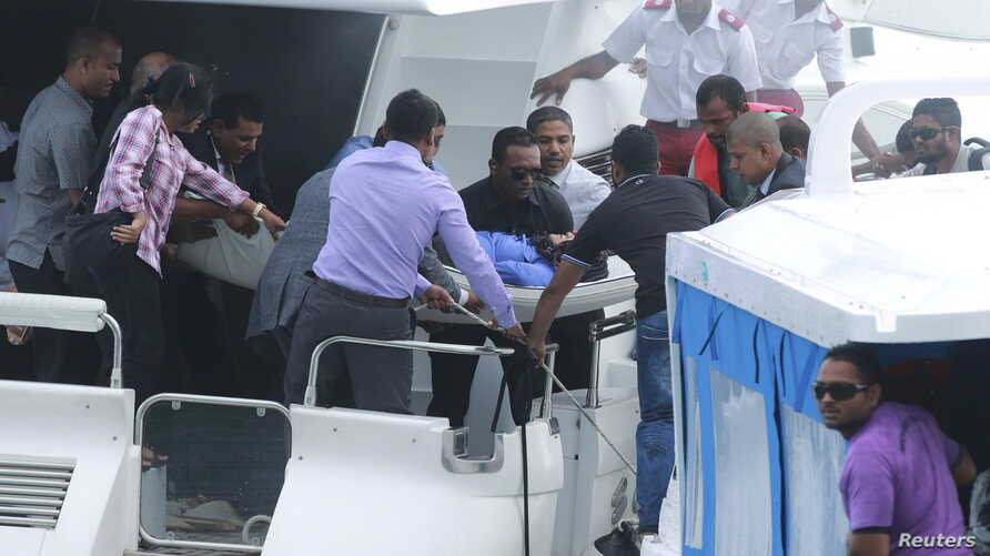 FILE - Officials carry an injured woman off the speed boat of Maldives President Abdulla Yameen Abdul Gayoom (not pictured) after an explosion onboard, in Male, Maldives, Sept. 28, 2015.