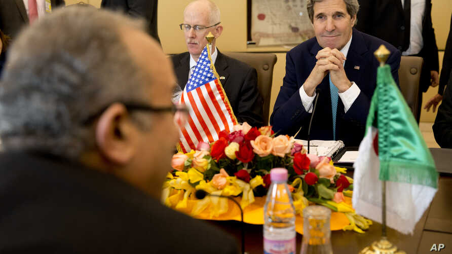 U.S. Secretary of State John Kerry, right, next to U.S. Ambassador to Algeria Henry Ensher, smiles as he listens to Algerian Foreign Minister Ramtane Lamamra, front left across table, Algiers, April 3, 2014.