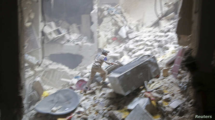A Civil Defense member looks for survivors at a site hit by what activists said were two barrel bombs dropped by forces loyal to Syria's President Bashar al-Assad in the Al-Shaar neighborhood of Aleppo, July 27, 2014.