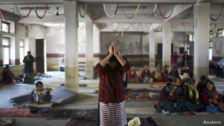 A Tibetan woman offers prayer upon her arrival during an event organized to express solidarity with the victims of violence in Tibet and to those who self-immolated to protest against Chinese rule in Tibet, in Kathmandu, November 17, 2012.