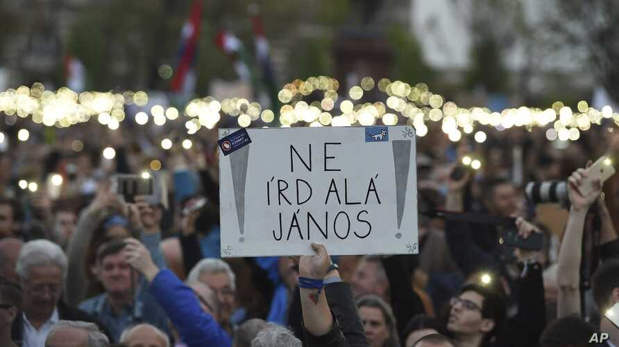 "Demonstrators hold a placard reading ""Don't sign it, Janos"" referring to President Janos Ader as they protest against the amendment of the higher education law seen by many as an action aiming at the closure of the Central European University, founde"
