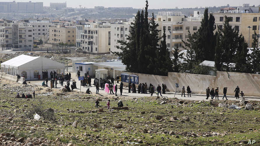 FILE - Refugees line up outside the U.N. refugee agency headquarters in Amman, Jordan, Feb. 5, 2017. Aid officials say Jordan has sent hundreds of Syrian refugees back to Syria since the beginning of the year, in what a rights group says is a violati