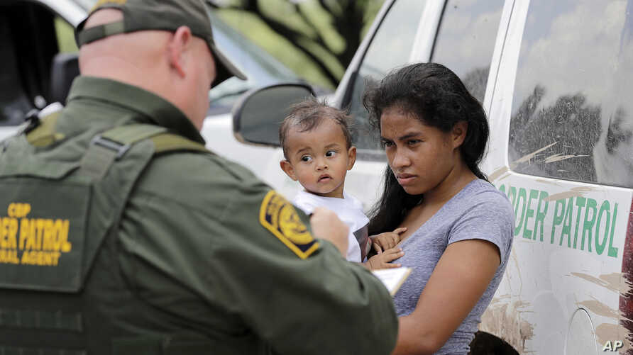 A mother migrating from Honduras holds her 1-year-old child as she surrenders to U.S. Border Patrol agents after illegally crossing the border near McAllen, Texas, June 25, 2018.