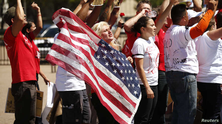 FILE - A woman holds up a U.S. flag as she other anti-deportation protesters chant in front of the White House in Washington.