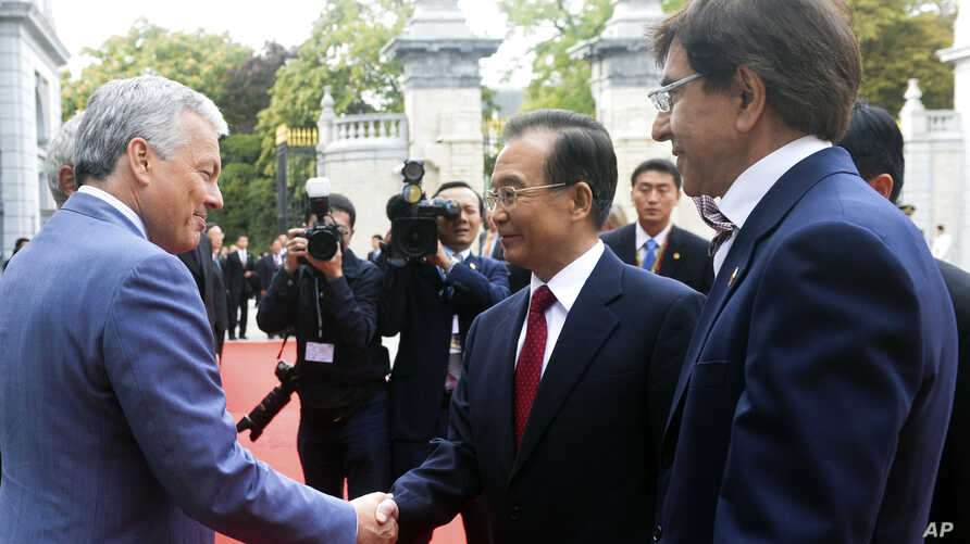 Chinese Premier Wen Jiabao, center, is greeted by Belgian PM Elio Di Rupo, right, and Belgian FM Didier Reynders prior to a meeting at the Egmont Palace in Brussels, September 20, 2012.