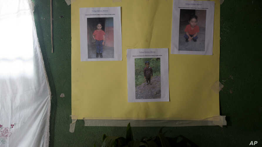 A poster with photocopies that show Felipe Gomez Alonzo is taped to a wall as part of a makeshift memorial honoring the 8-year-old, inside his mother's home in Yalambojoch, Guatemala, Dec. 29, 2018.