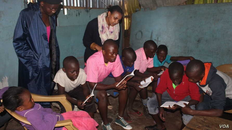 Betty Mutua, founder of Sauti ya Vitabu, looks on as children read books at one of the organization's pop-up centers. (R. Ombuor/VOA)