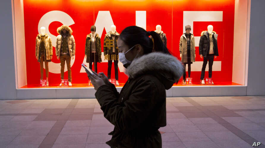FILE - A woman walks past mannequins promoting a sale outside a retail outlet in Beijing, China, Dec. 16, 2016. China's economic growth ticked up in the final quarter of 2016, but its full-year performance was the weakest in three decades.