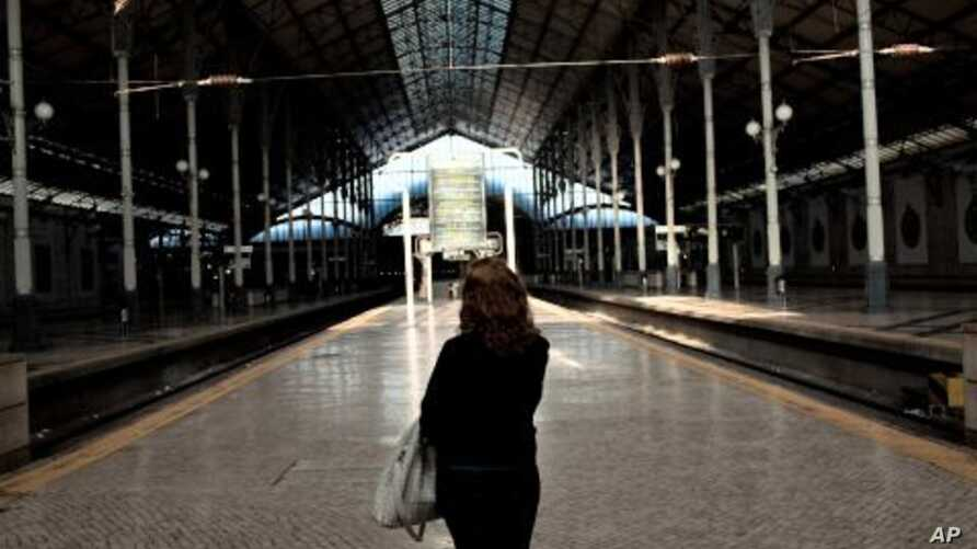 A woman looks at a sign announcing the disruption of train services at an empty Rossio train station in Lisbon, November 24, 2011.