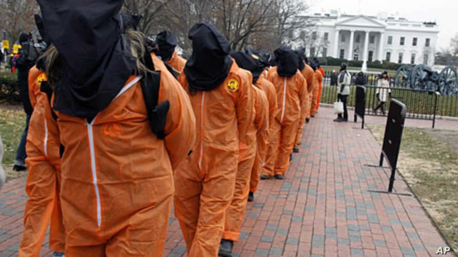 Protesters seeking closure of the Guantanamo Bay detention facility wear orange jumpsuits and black hoods as they demonstrate outside the White House, 11 Jan 2011