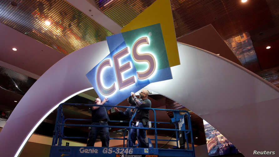 Workers hang signage in the lobby of the Las Vegas Convention Center as they prepare for the 2017 International CES technology trade show in Las Vegas, Nevada, Jan. 3, 2017.