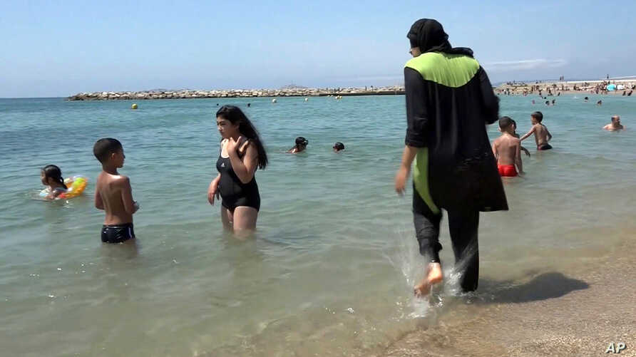 FILE - In this Aug.4 2016 file photo made from video, Nissrine Samali, 20, gets into the sea wearing traditional Islamic dress, in Marseille, southern France. The French resort of Cannes has banned full-body, head-covering swimsuits worn by some Musl...