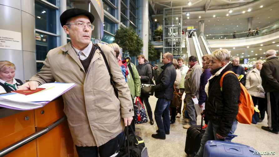 Passengers, whose flights to Egypt were suspended, gather at an information desk of Domodedovo airport outside Moscow, Russia, Nov. 6, 2015.