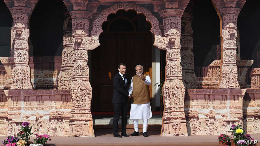 Indian Prime Minister Narendra Modi (R) welcomes French President Emmanuel Macron to the founding conference of the International Solar Alliance in New Delhi on March 11, 2018.