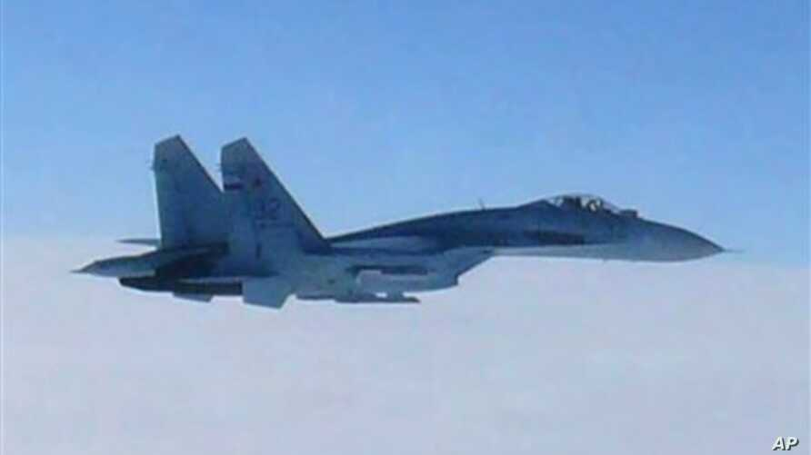 In this photo taken by Japan Air Self-Defense Force and released by the Joint Staff Office of the Defense Ministry of Japan, a Russian fighter jet SU-27 flies over the sea off the Japanese island of Hokkaido Thursday afternoon, Feb. 7, 2013. The Defe