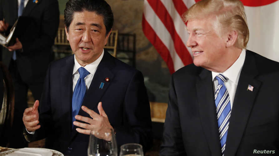 U.S. President Donald Trump looks on as Japan's Prime Minister Shinzo Abe speaks while dining at Trump's Mar-a-Lago estate in Palm Beach, April 18, 2018.