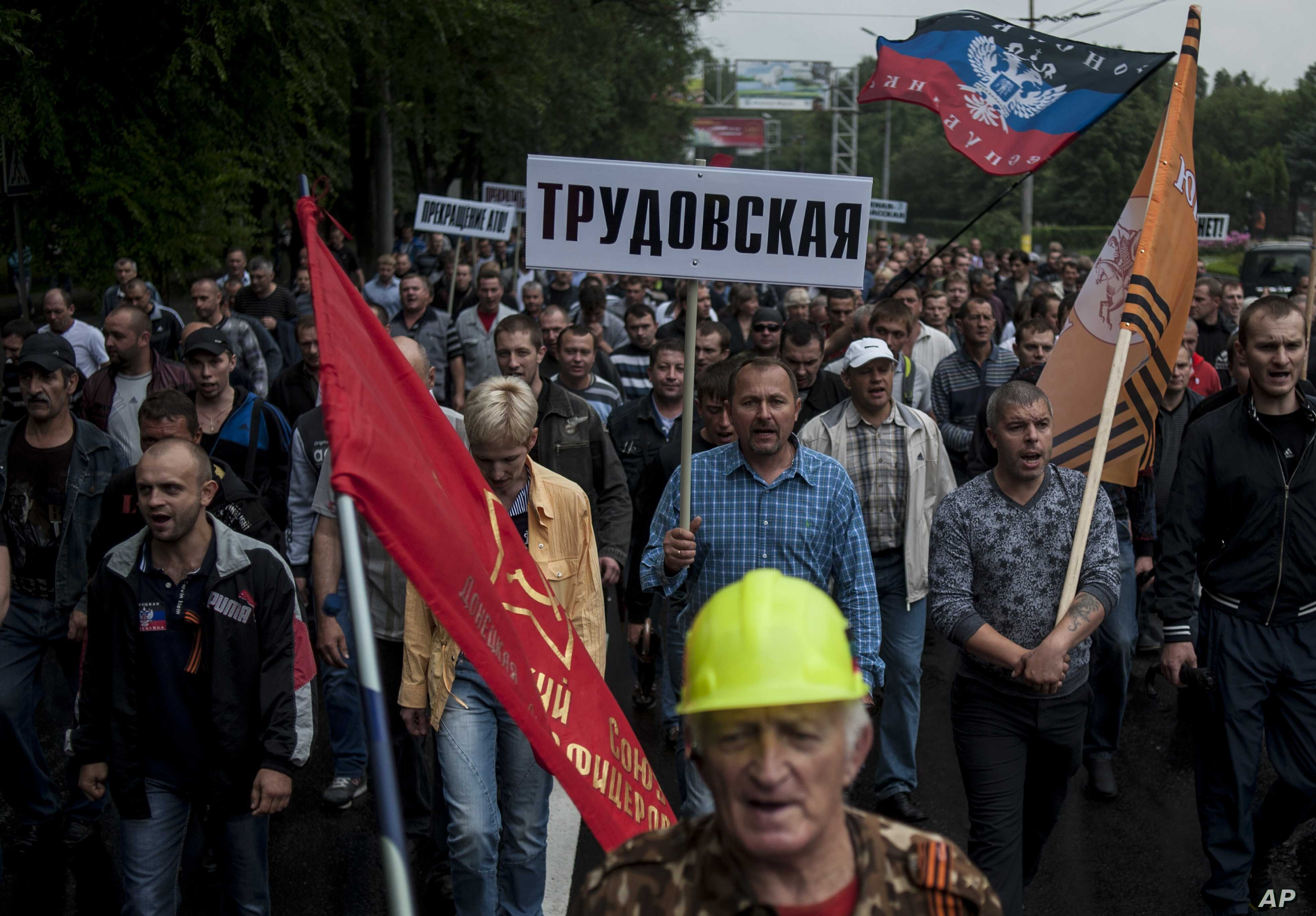 Miners, one of them carrying a sign with the name of the mine Trudovskaya, march in support of peace in Donetsk, eastern Ukraine, June 18, 2014.