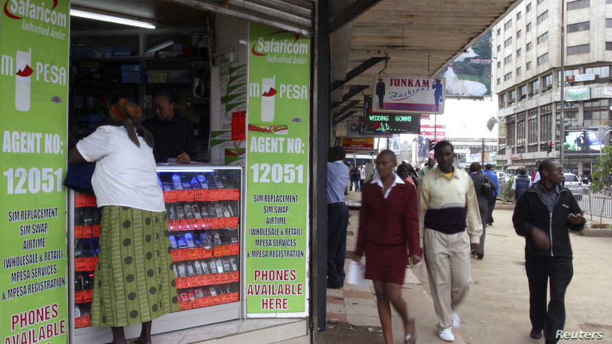 Pedestrians walk past an M-Pesa shop in downtown Nairobi, Kenya, May 12, 2009.