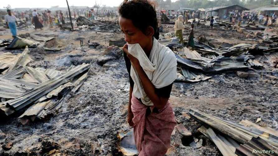 A woman walks among debris after fire destroyed shelters at a camp for internally displaced Rohingya Muslims in the western Rakhine State near Sittwe, Myanmar