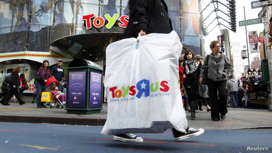 FILE - Shoppers pass by the Toys R Us store at Times Square in New York.