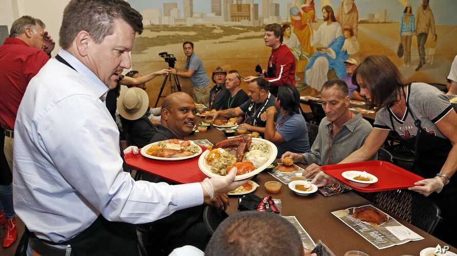 Arizona Cardinals team president Michael Bidwill, left, joins other players and staff of the Cardinals NFL football team as they serve Thanksgiving dinner at the Phoenix Rescue Mission at the 15th annual 'Feed the Hungry' event, Nov. 21, 2016, in Pho