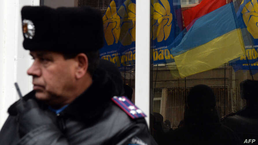 A Ukrainian police officer stands by as the flags of radical party Svoboda (Freedom) are reflected in the window during a protest against political repression in front of the Ukrainian Interior Ministry headquarters in Kiyv, Nov. 28, 2013.