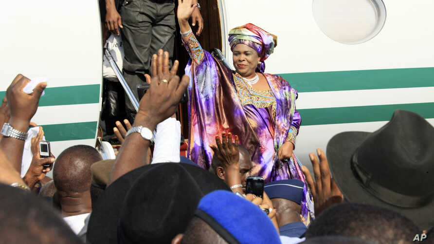 FILE - Patience Jonathan, wife of former Nigeria President Goodluck Jonathan, waves to the crowd upon her arrival at Nnamdi Azikiwe International Airport, in Abuja, Nigeria, Oct. 17, 2012. She is claiming ownership of bank accounts allegedly worth $3