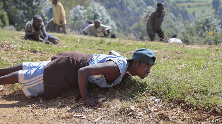 Demonstrators opposed to a third term for President Pierre Nkurunziza in Burundi dive to the ground as army soldiers shoot in the air to disperse the protest, in the rural area of Mugongomanga, east of the capital, Bujumbura, June 10, 2015.